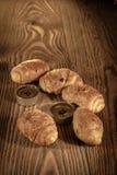 Cruasanes, pasteles, molletes, tortas y pasteles en un fondo de madera hermoso con las velas 1 Foto de archivo