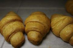 Cruasanes recientemente cocidos en el horno de la hornada Imagen de archivo