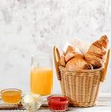 Cruasanes y bollo del desayuno de la hornada en cesta con el zumo de naranja, miel, mantequilla, atasco de frambuesa en la tabla  Fotografía de archivo