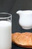 Cruasanes y vidrio de leche fresca con el leche-jarro en viejo fondo de madera rústico Fotografía de archivo libre de regalías