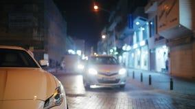 Cruce con los coches móviles y la gente que cruzan el camino en la noche almacen de video