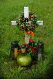 Cruce con una guirnalda y las velas, una tumba foto de archivo