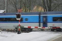 Cruce ferroviario checo en el invierno con el tren en una nevada Fotos de archivo