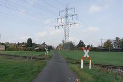 Cruce ferroviario en un pequeño pueblo delante de una torre de alto voltaje imagenes de archivo