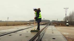 Cruce ferroviario limpio del trabajador ferroviario de sexo femenino en invierno almacen de metraje de vídeo