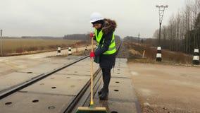 Cruce ferroviario limpio del trabajador ferroviario de sexo femenino y tomar la rotura metrajes