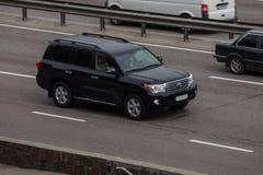 Crucero de lujo de la tierra de Toyota del negro del coche que apresura en la carretera vacía fotos de archivo