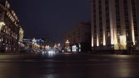 Cruces de la ciudad de la noche La arquitectura majestuosa, coches conduce de izquierda a derecha almacen de video