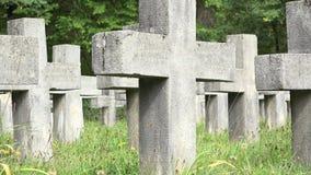 Cruces frías de las lápidas mortuarias e hierba verde fresca en cementerio cristiano metrajes