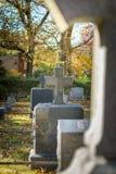 Cruces y lápidas mortuarias entre hierba y hojas caidas, en un día del otoño en el cementerio del Sleepy Hollow, en el norte d fotografía de archivo