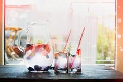 Cruche avec l'eau, les glaçons et les baies, deux verres sur la table de cuisine au-dessus du fond de terrasse de jardin Photographie stock