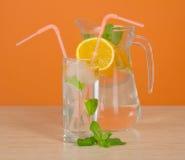 Cruche avec la boisson, le verre et une tranche orange Image libre de droits