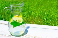 Cruche avec la limonade du citron et des tapis avec de la glace sur un fond d'herbe verte le concept des boissons non alcoolis?es image libre de droits