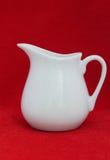 Cruche blanche de porcelaine sur le tissu rouge Photos stock