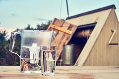 Cruche de filtre d'eau et une tasse d'eau propre en verre transparente devant le puits d'aspiration en bois dehors dans la soirée images libres de droits