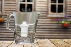 Cruche de filtre d'eau se tenant sur une table en bois rugueuse devant une maison de campagne dehors photo stock