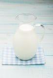 Cruche de lait sur une nappe à carreaux bleue Photo stock