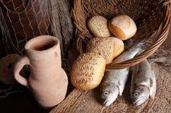 Cruche de vin avec du pain et des poissons Photos stock