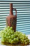 Cruche de vin et de raisins Photographie stock