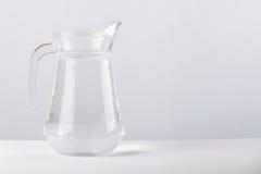 Cruche en verre avec de l'eau d'isolement sur le fond blanc Photographie stock