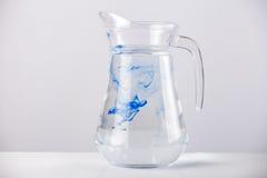 Cruche en verre avec de l'eau d'isolement sur le fond blanc Image stock