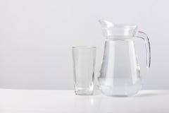 Cruche en verre avec de l'eau d'isolement sur le fond blanc Photos stock