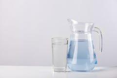 Cruche en verre avec de l'eau d'isolement sur le fond blanc Images stock