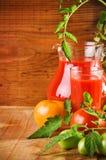 Cruche et glace avec le jus et les tomates de tomates Photographie stock