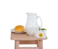 Cruche et petit pain de lait du plat Photographie stock
