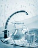 Cruche et tasse en verre avec de l'eau Photos libres de droits