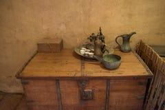 Cruche, plat, tasses, sauser et théière antiques sur la table Images libres de droits