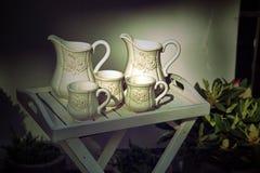 Cruches et tasses de lait blanches Photographie stock