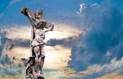 Crucified Jesus Christ against dramatic sunset. Marble Holy cross with crucified Jesus Christ against dramatic sunset Royalty Free Stock Photos