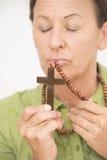 Crucifijo cristiano que se besa de la mujer religiosa Foto de archivo libre de regalías