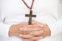 Crucifijo cristiano y manos de rogación Foto de archivo libre de regalías