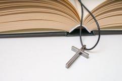 Crucifijo metálico y Sagrada Biblia abierta Fotografía de archivo libre de regalías