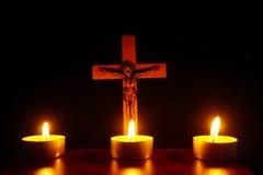 Crucifijo y tres velas ardientes en la oscuridad Ruegue a Jesu imagen de archivo