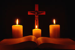 Crucifix και τρία καίγοντας κεριά με την ανοικτή Βίβλο στον πίνακα στο τ Στοκ Εικόνες