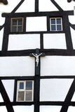 Crucifix against facade of a half-timbered house Stock Photo