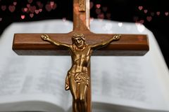 Crucifix ahead of open Bible with red hearts stock photography