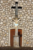 Crucifix before a chapel Royalty Free Stock Image