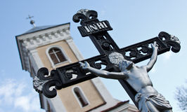 Crucifix and church tower Stock Photography