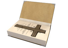 Crucifix Concealed In A Bible. An open hardback bible with a cutaway area in the pages concealing a wooden crucifix on an isolated background Stock Photography