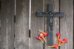 Crucifix en bois noir sur la planche en bois minable avec le flowe rouge Photo libre de droits