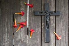 Crucifix en bois noir sur la planche en bois minable avec le flowe rouge Image libre de droits