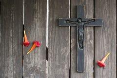 Crucifix en bois noir sur la planche en bois minable avec les fleurs rouges Photo libre de droits