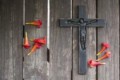 Crucifix en bois noir sur la planche en bois minable avec les fleurs rouges Photos stock