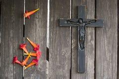 Crucifix en bois noir sur la planche en bois minable avec les fleurs rouges Photos libres de droits