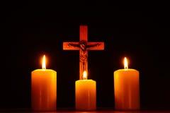 Crucifix et trois bougies brûlantes dans l'obscurité Priez à Jesu Photo stock