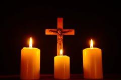 Crucifix et trois bougies brûlantes dans l'obscurité Priez à Jesu Photos libres de droits